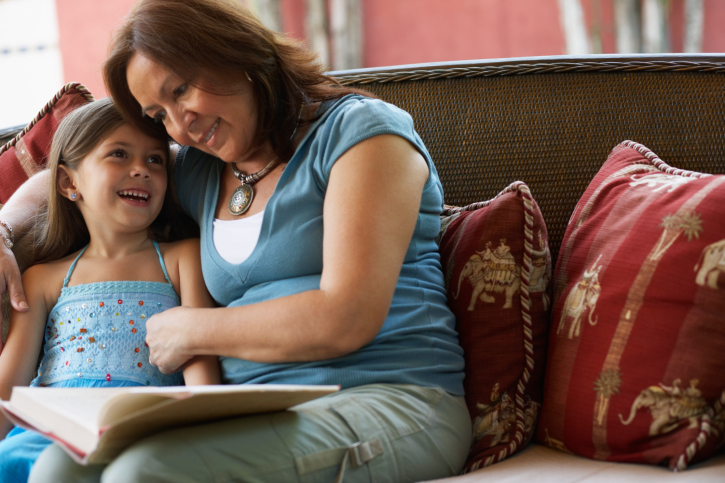 Latino mother reading with daughter